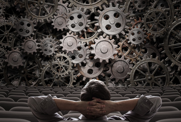 Conceptual image of businessman looking to working gears sitting in auditorium
